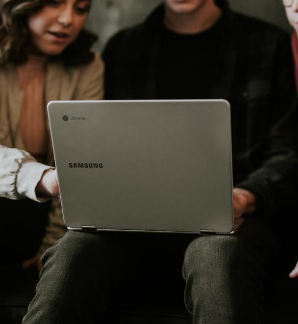 Kolme ihmistä istuu sohvalla, keskimmäisellä kannettava tietokone sylissä, kaikki katsovat näyttöä.