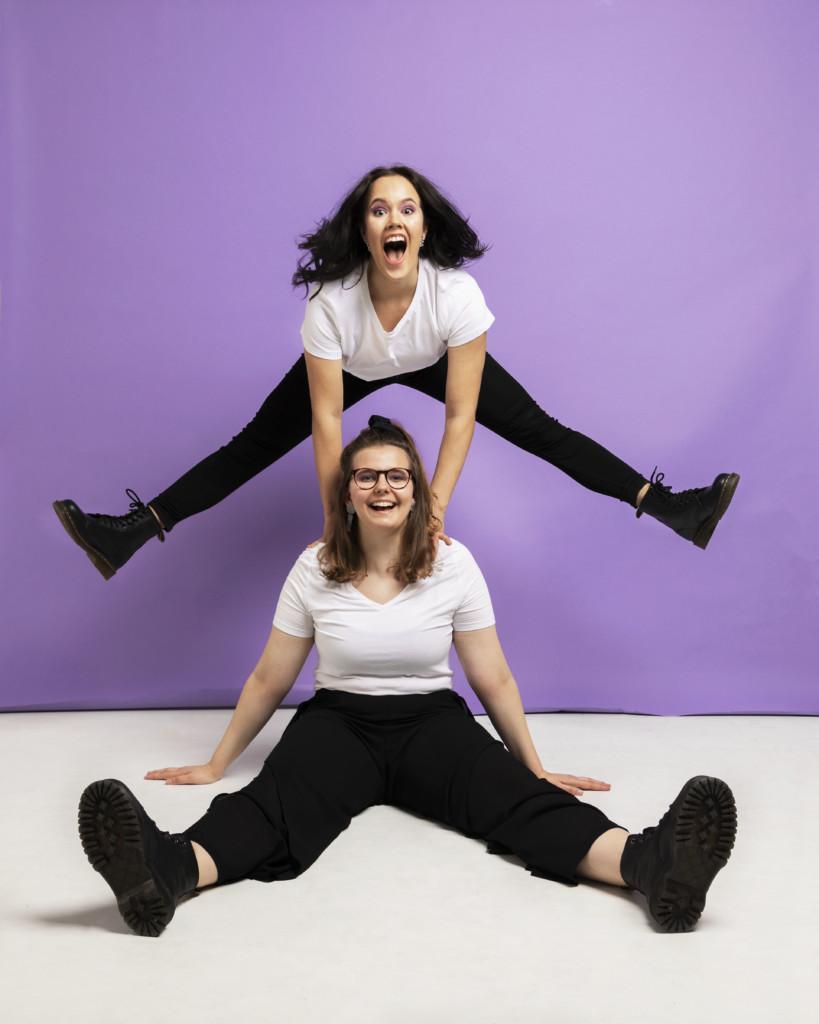 Kaksi nuorta naista, joista toinen istuu lattialla ja toinen on takana ja hyppää ilmaan jalat auki. Violetti tausta ja valkoinen lattia.