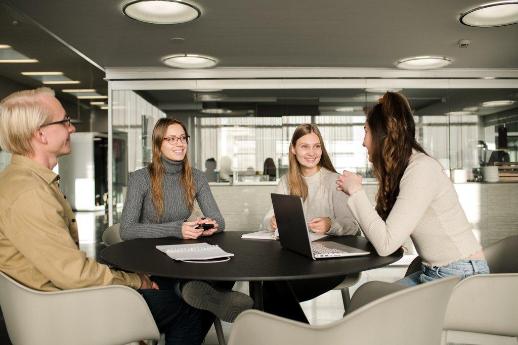 A group of students conversating around a round table