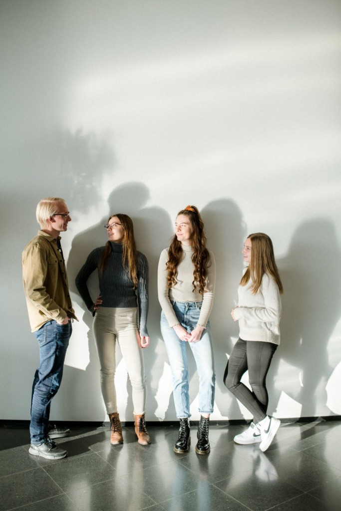 Four students standing side by side in front of a white wall