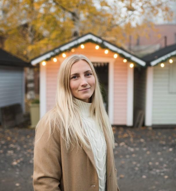 Nainen seisoo ulkona, taustalla pastellinvärisiä pikkumökkejä