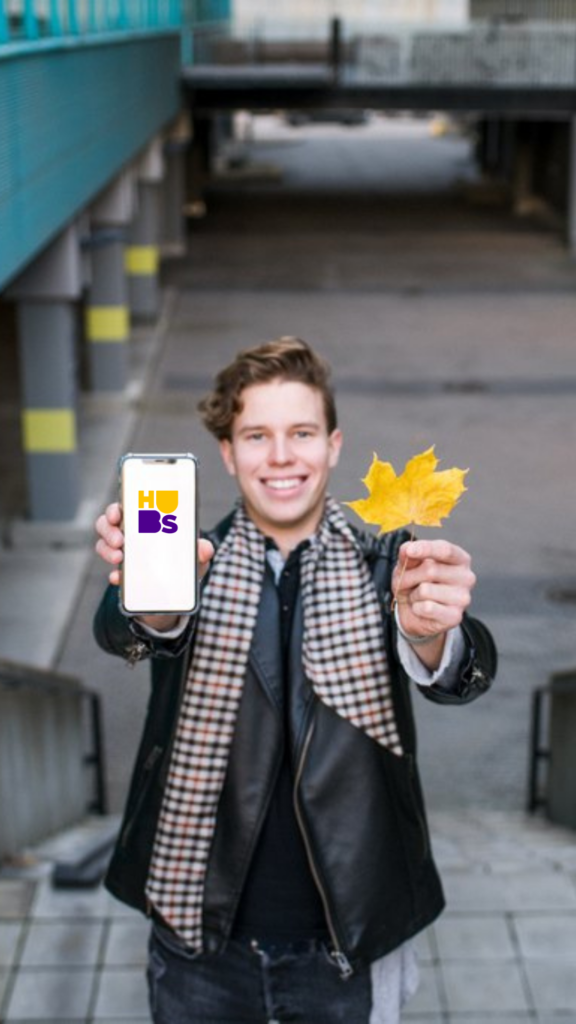 A standing man holding a phone and a yellow maple leaf