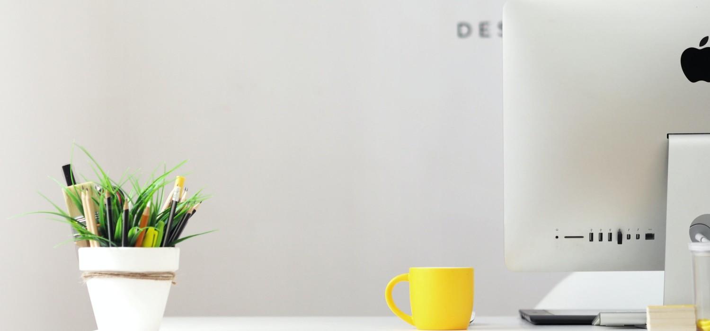 Kuvituskuva: tietokone, kahvikuppi ja viherkasvi.