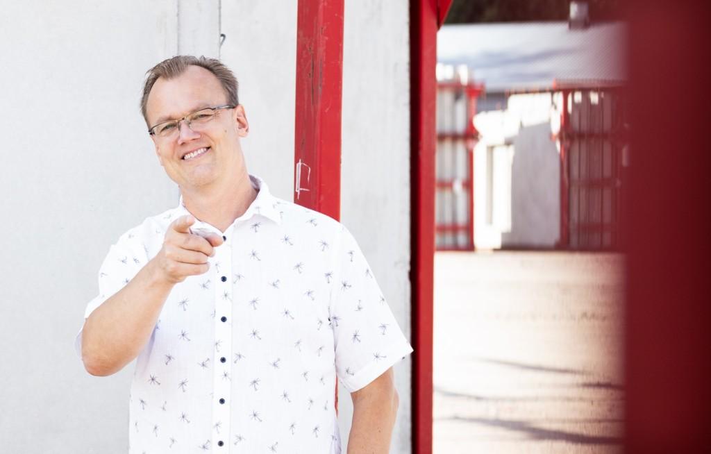 Antti Leijala seisoo valkoisen seinän edessä, jossa punaisia tehosteita ja osoittaa etusormellaan kameraa kohti
