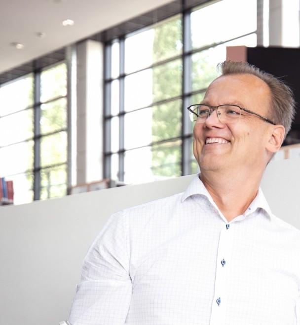 Yrittäjä Antti Leijala seisoo vaaleassa tilassa, taustalla isoja ruutuikkunoita