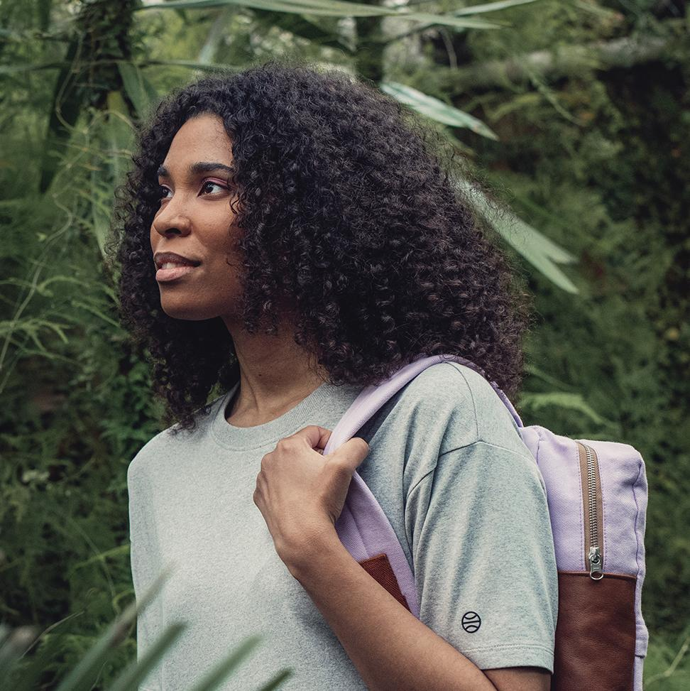 A woman in grey t-shirt carrying a back bag on her left shoulder. Green plants on the background.
