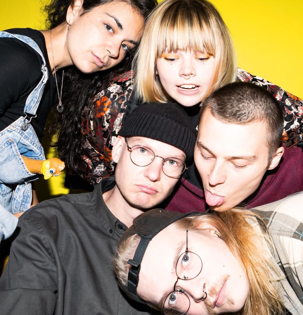 Viisi nuorta ihmisistä lähekkäin erilaisissa asennoissa, takana keltainen tausta