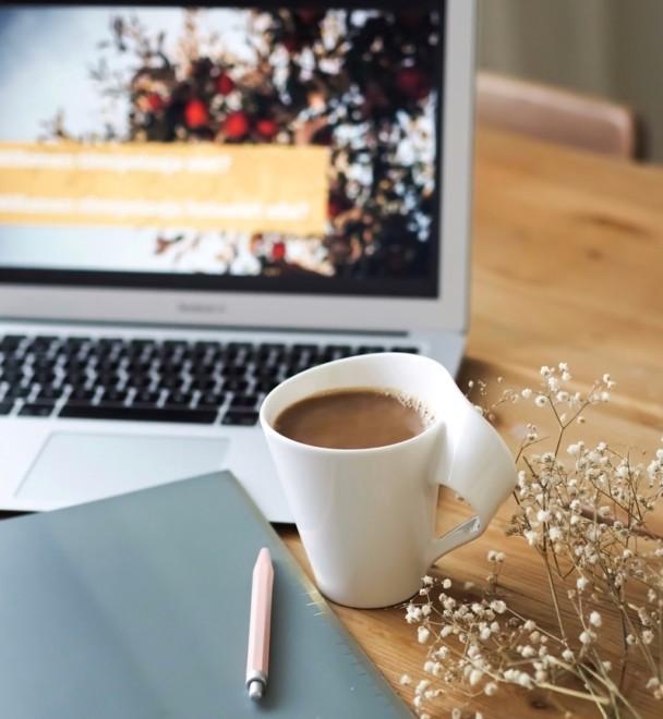 Vihko ja kynä, kahvikuppi ja taustalla kannettava tietokone.