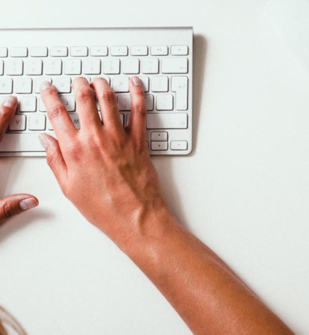 Kädet valkoisella tietokoneen näppäimistöllä.