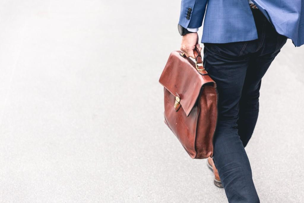 Takaa otettu kuva miehen alavartalosta kävelemässä, vasemmassa kädessä ruskea nahkasalkku.