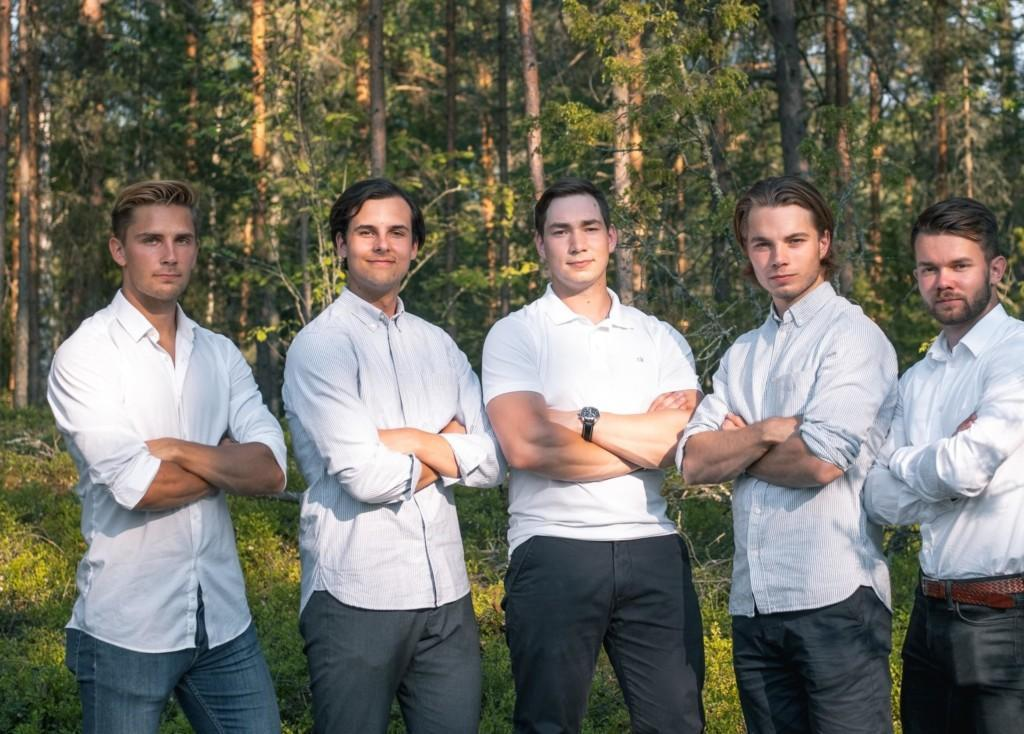 Brightlife tiimin viisi jäsentä seisoo rivissä kädet ristissä valkoisissa paidoissa ja tummissa housuissa. Taustalla vehreä metsä.