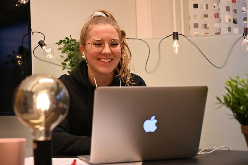 A student smiling with headphones on, sitting by a table and a laptop.