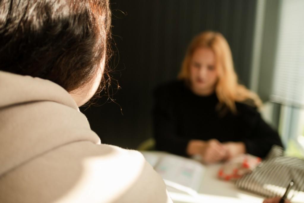 Etualalla henkilön olkapää ja hiukset takaa kuvattuna, taustallaNainen mustassa paidassa pöydän ääressä